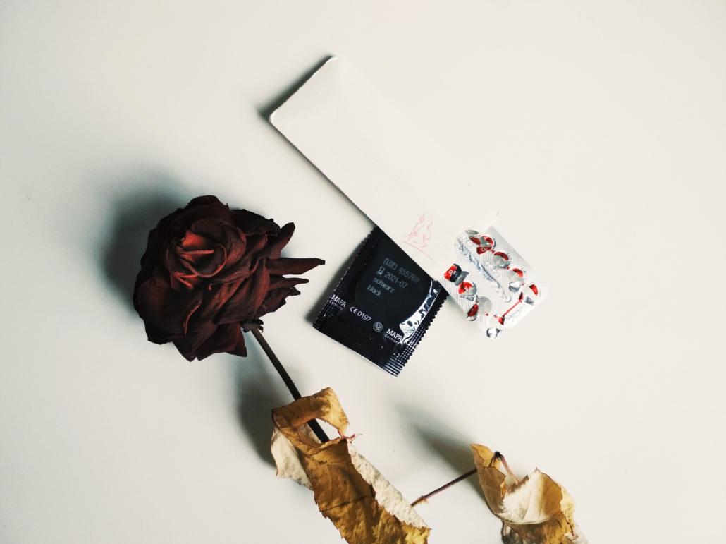 Kondom und Pille neben Rose